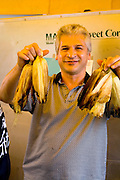 Man age 45 in food booth holding up freshly roasted corn on the cob Grand Old Day Street Fair St Paul Minnesota USA