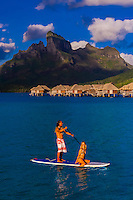 A couple rowing around the lagoon on a paddleboard, Four Seasons Resort Bora Bora, French Polynesia.