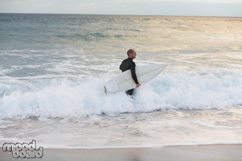 Surfer carrying surfboard in sea side view