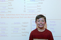 Schoolboy standing in classroom, projection screen behind him