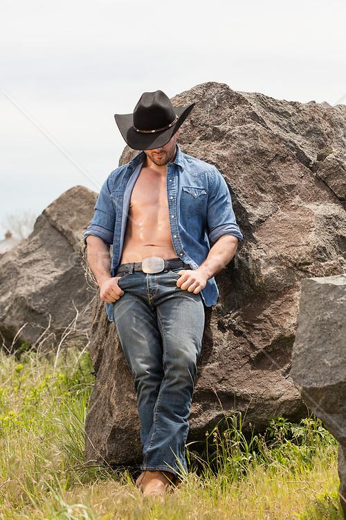 muscular cowboy with an open shirt outdoors against rocks