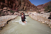 Female hiker cooling of in the flowing water of Wadi Zered (Wadi Hassa or Hasa) in western Jordan. A sand stone canyon with fresh running water. Flowing into the Dead Sea