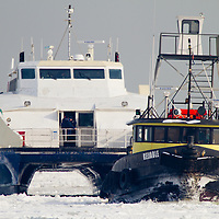 "The Tug Boat ""Reliable"" escorts the New York Waterway Fast Ferry 'Finest' through a iced over Raritan Bay to it's home port of Belford NJ.   A extended period of sub freezing temperatures iced over much of New York Harbor creating issues for commuter ferries and commercial marine traffic."