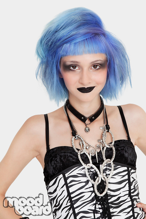 Portrait of young female punk with dyed hair over gray background