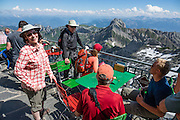 Dining deck. Berggasthaus Alter Säntis is perched dramatically atop Säntis (2502 m / 8218 feet), the highest peak of the Alpstein range and the Appenzell Alps, located in northeast Switzerland, Europe. Shared by three cantons, Säntis can be reached easily via aerial tramway (Luftseilbahn) from Schwägalp, or with effort via wonderful trails, to see vast mountain views across six countries: Switzerland, Germany, Austria, Liechtenstein, France and Italy. At center is Altmann peak (2435m), second highest of the Appenzell Alps. We highly recommend staying overnight on top of Säntis as we did at Berggasthaus Alter Säntis, a fifth-generation family-run mountain inn since 1850, offering modern private double and dormitory lodging with good food and magnificent views. From where we joined it at Rotsteinpass, the spectacular, rocky Lisengrat trail to Säntis is rigged with safety cables in case of icy or wet conditions (and can be scary for those with fear of heights). In rainy weather the next day, we took the easy tram down to Schwägalp instead of hiking to Ebenalp. The Appenzell Alps rise between Lake Walen and Lake Constance. For licensing options, please inquire.