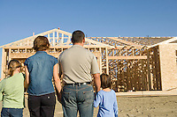Family with two children (6-9) at construction site, back view