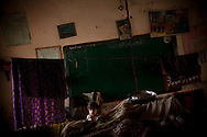 A young boy stands in a classroom that his now his family shelter, after his family fled their village from rising flood waters, on 10 September, 2011, in Badin, Pakistan. More than 17% of children in the flood areas are severely acutely malnourished and 67% of livestock has been destroyed after torrential monsoon rains, reminiscent of the 2010 floods that devastated Pakistan, have reportedly already killed over 200 people, left 300,000 homeless and affected over 7 million. (Photo by Warrick Page)