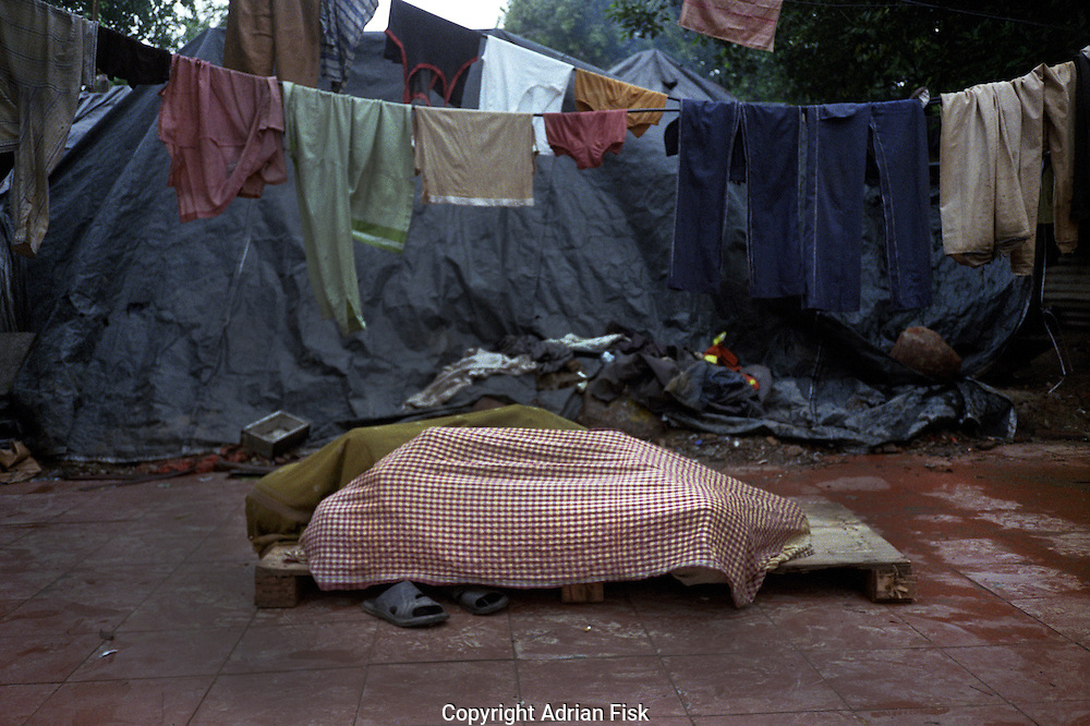 Common Wealth games workers protect themselves from rain whilst sleeping.