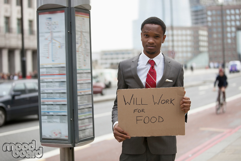 Young businessman holding Will Work for Food sign at street