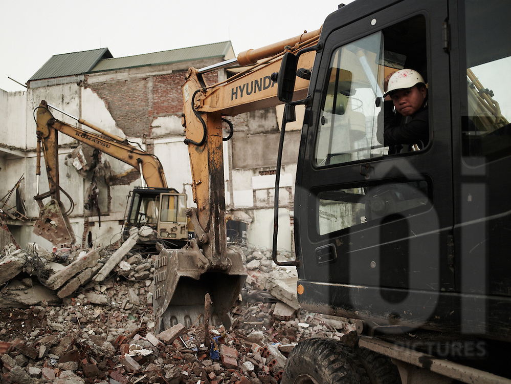 A worker in his excavator demolishes houses in Hoang Hoa Tham street, Hanoi, Vietnam, Asia