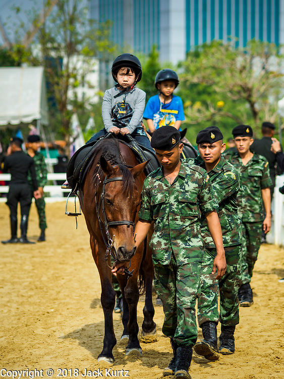 """13 JANUARY 2018 - BANGKOK, THAILAND:  Thai soldiers help children on Thai cavalry horses during Children's Day activities at the Royal Thai Army's King's Guard 2nd Cavalry Camp in central Bangkok. Children's Day is called """"Wan Dek"""" in Thai. Many government offices and military bases hold special activities for children as do shopping malls.      PHOTO BY JACK KURTZ"""