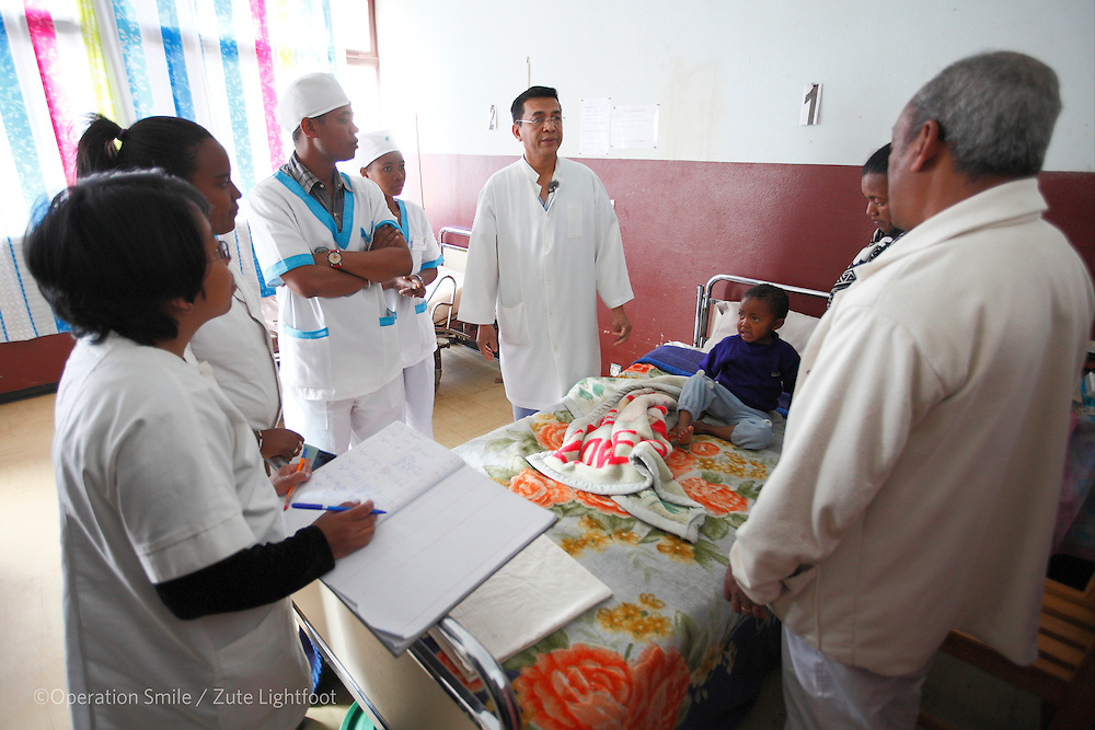 General Surgeon Dr RANDRIAMIHAJA Pierrot talks with the family of <br /> FANAMBINANJANAHARY Fenomamama Fandresena, 3 years old, male, scheduled for a hernia operation who are waiting in the pre op  private ward at Antsirabe Hospital. Antsirabe Clinic Project sponsored by the Swedish Postal Code lottery. Madagascar. September 2015.<br /> (Operation Smile Photographer &ndash; Zute Lightfoot)