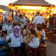 "People dining outside in Istanbul, Turkey. In the evening in Istanbul, brightly lit fish boats beckon with a promise of a savory treat. For about a century, fishermen have been bringing their catch from the Bosphorus and the Sea of Marmara to Istanbul's Galata Bridge over the Golden Horn for sale. Shouting: ""Balık ekmek! Balık ekmek!"" (Fish in bread! Fish in bread!) a lively scene unfolds bt the water."