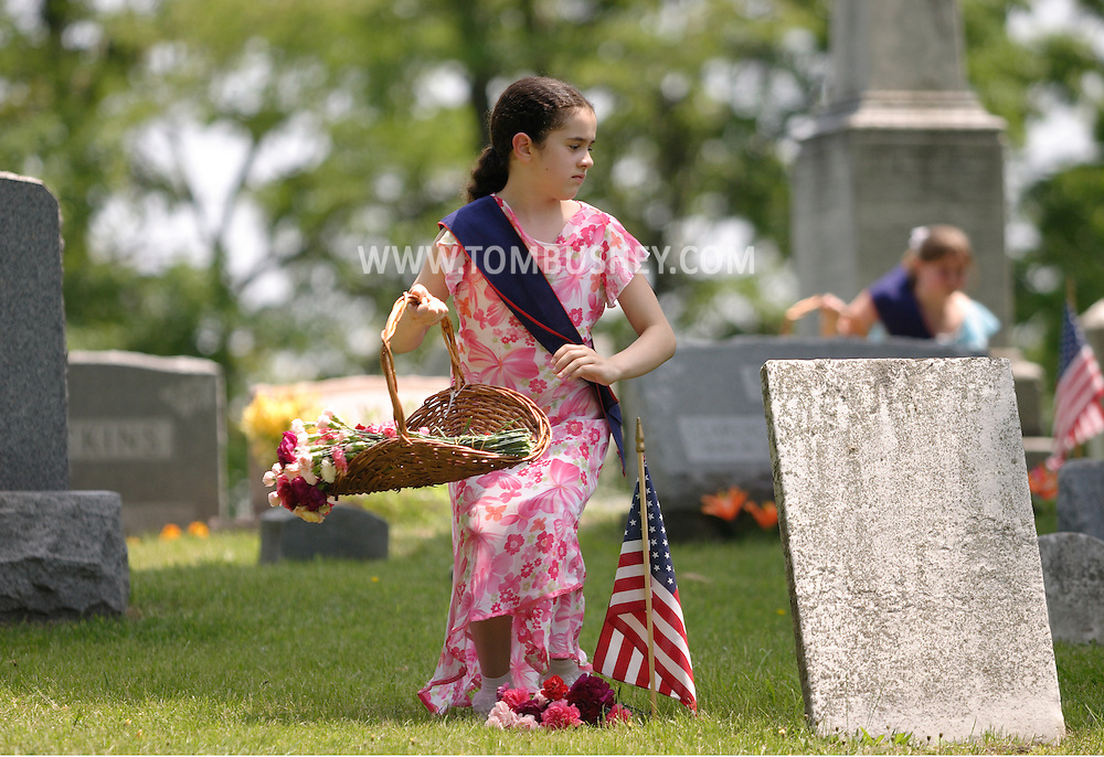 Hamptonburgh, N.Y. - A young girl stands up after placing flowers on a veteran's grave during a Memorial Day services at Hamptonburgh Cemetery on May 29, 2006.