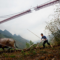Farmer Wei Xinyuan ploughs his field under the Baling River Bridge, which soars 400 meters above the river valley. The bridge, in this image its platform span just about to be linked, is a feat of modern engineering. The Baling River Bridge is one of hundreds of infrastructure projects on which China plans to spend about 310 billion euros on over the next several years.