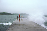 Fisherman braves bad weather as a wave breaks over a jetty in North Wales....travel, lifestyle