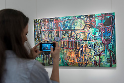 "© Licensed to London News Pictures. 29/03/2019. LONDON, UK. A visitor views ""Untitled"", by Abdoulaye Aboudia Diarrassouba (Est. GBP 10,000-15,000). Preview of Sotheby's upcoming Modern and Contemporary African Art sale.  Works from artists across the African diaspora will be offered for sale on 2 April.  Photo credit: Stephen Chung/LNP"