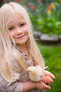 Portrait of cute young girl with baby chicken in a rural garden setting.
