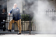 A floor trader takes a cigarette break outside tne NYSE Euronext Stock Exchange on Wall Street. He is halfway hidden by the steam leaking from the underground steam power pipes that provide many Manhattan office buildings with cooling power.