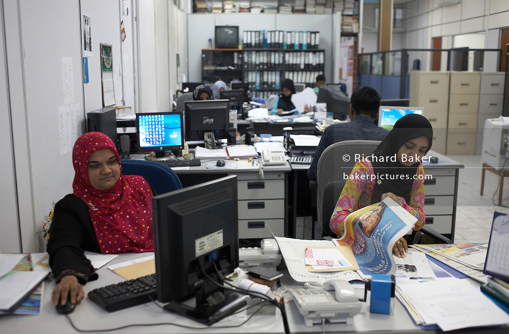 Mixed gender office with men working alongside ladies wearing the hejab at Fisheries Ministry of the Maldives government