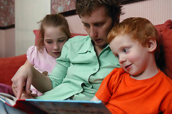 Single parent reading a story to her two young children,