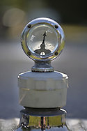 Westbury, New York, USA. June 12, 2016.  Wilmot-Breeden car radiator cap Calormeter temperature gauge with transparent dial, seen in close up on hood of vintage car, is at the Antique and Collectible Auto Show at the 50th Annual Spring Meet at Old Westbury Gardens, in the Gold Coast of Long Island, and sponsored by Greater New York Region, GNYR, Antique Automobile Club of America, AACA. Participating vehicles in the judged show included hundreds of domestic and foreign, antique, classic, collectible, and modern cars.