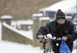 © Licensed to London News Pictures. 20/01/2013.More snow in Kent as this cyclist is having to push his bike after a visit to the shops..Snow continues to fall in Orpington, Kent over night and today (20.01.2013).. Photo credit : Grant Falvey/LNP