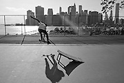 A skater jumping from a platform with the Manhattan skyline in the background, Brooklyn, New York