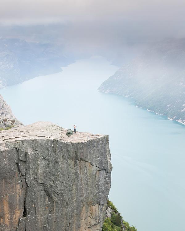 Person kommer ut av teltet på Preikestolen over Lysefjorden, Forsand, Rogaland.<br /> <br /> Waking up on the Pulpit Rock 604 meters above the Lysefjorden, Rogaland, Norway.