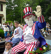 """A man dressed as """"Uncle Sam"""" waves to the crowd during the Doylestown Memorial Day parade, Monday, May 27, 2002, in Doylestown, Pa. (Photo by William Thomas Cain/photodx.com)"""
