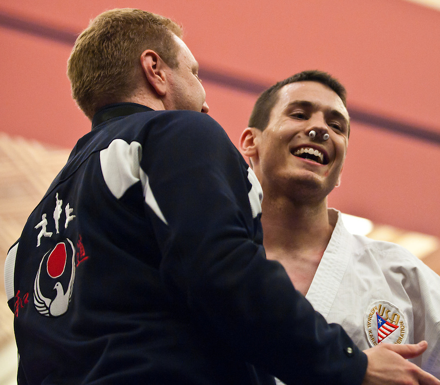 Tom Scott gets hugs from Coach Brody Burns after winning Gold