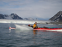 A kayak paddler by a glacier calf on Spitzbergen