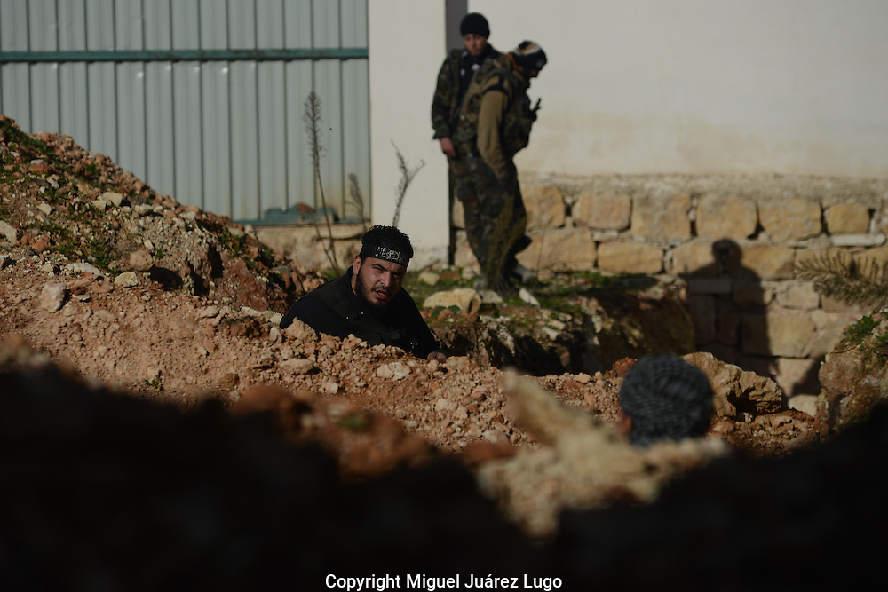 Aleppo, Syria, December, 2012 -  Free Syria Army rebels, dug into trenches, talk during an operation to advance toward the airport where more than 1500 Syrian government soldiers, 20 MIG jets and 40 helicopters have been based for months, wreaking havoc on the city. Taking the airport is a critical goal for the rebels. (Photo by Miguel Juárez Lugo)