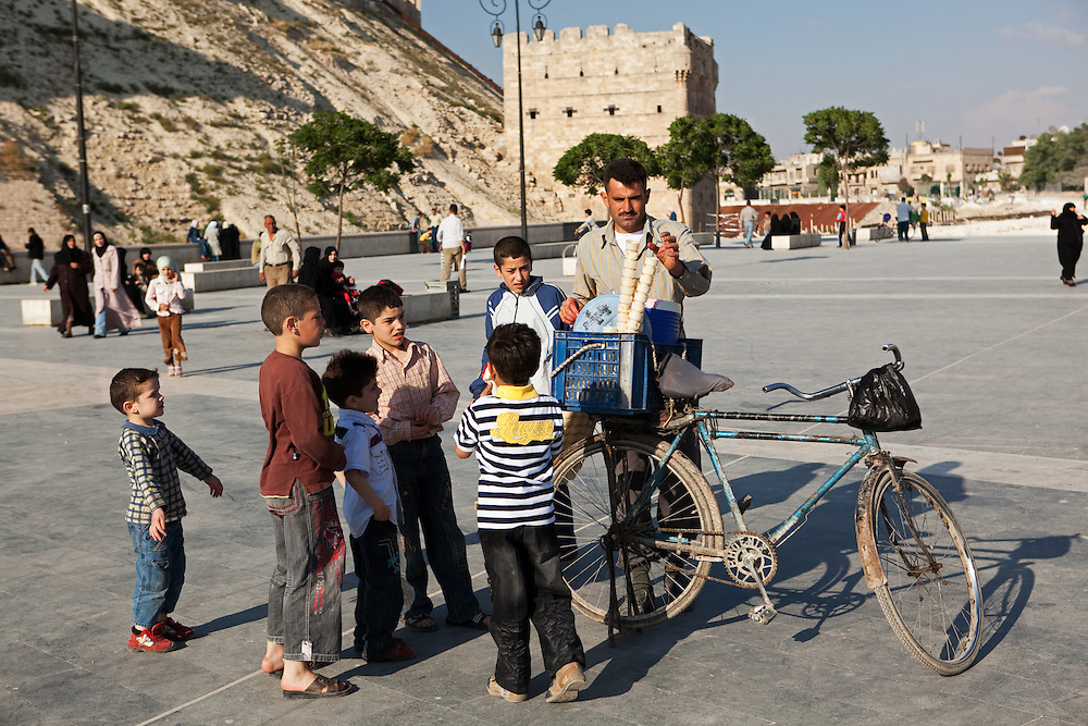 Children gather around an ice cream vendor (bicycle), outside the Citadel, Aleppo, Syria