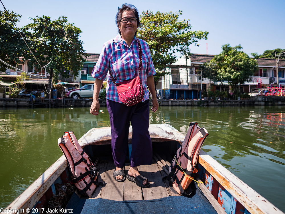 16 FEBRUARY 2017 - THEPHARAK, SAMUT PRAKAN, THAILAND: Passengers in a small boat that serves as a ferry taking people across Khlong Samrong, in the Bangkok suburbs. The boatman pulls it across using a system of ropes and pulleys. The boatman has been working on the boat since he was a child. Small ferries like this used to be common in Bangkok but many of the khlongs (the canals that used to crisscross Bangkok) have been filled in and bridges have been across the remaining khlongs. Now there are only a handful of the ferries left. This ferry charges 2 Baht (the equivalent of about .06¢ US) per person to take a person across the khlong.      PHOTO BY JACK KURTZ