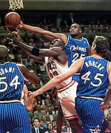 Chicago Bulls vs Orlando Magic- NBA Eastern Conference Championship- 5/19/96-- Chicago's Michael Jordan (23), middle, stretches for the basket in the first half. Behind him is Orlando's Nick Anderdson (25). At left is Orlando's Horace Grant (54) and at right is Orlando's Jon Koncak (45).