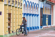 A cyclist rests in front of colorful colonnade style buildings in Tlacotalpan, Veracruz, Mexico. The tiny town is painted a riot of colors and features well preserved colonial Caribbean architectural style dating from the mid-16th-century.