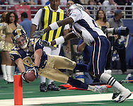 St. Louis Rams wide receiver Kevin Curtis (83) stretches to get the ball over the goal line, but is pushed out of bounds by New England's Randal Gay (R) during the fourth quarter.  The Patriots beat the Rams 40-22, in St. Louis, November 7, 2004.
