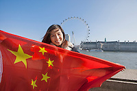 Portrait of happy young woman holding Chinese flag against London Eye at London; England; UK
