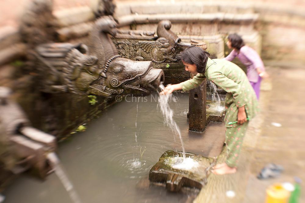 Two girls brush their teeth at public fountain in Patan's Durbar Square, Nepal.