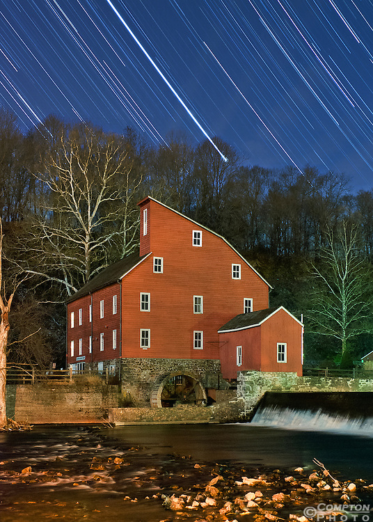 Illustration of the paths of stars and planets moving in the sky behind the Clinton Red Mill. The brightest line in the center of the sky happens to be the path of Jupiter over 90min.