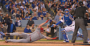 Reds Jay Bruce #32 dives back to the plate, but had been  tagged out by Los Angeles Dodgers catcher Yasmani Grandal #9 when he tried to stretch a triple into a home run in the 4th inning. Reds Brandon Phillips was driven in on the play.  The Los Angeles Dodgers played the Cincinnati Reds at Dodger Stadium in Los Angeles , CA.  May 25, 2016. (Photo by John McCoy/Southern California News Group