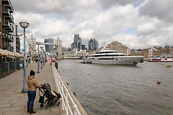 © Licensed to London News Pictures. 29/03/2018. London, UK. A woman and child look at the 220ft custom luxury superyacht, 'Global' moored at Butlers Wharf near Tower Bridge during a London visit. Previously named, Kismet during her last central London visit, she underwent a refit which saw her moved up 51 places in Boat International's list of top 200 largest super yachts in the world, boasting numerous luxuries such as a helipad, cinema and jacuzzi. Believed to be owned by Fulham Football Club chairman, Shahid Khan, Global can be chartered for an estimated £1m per week. Powered by 2 Caterpillar (3512 B) 2,038hp diesel engines and propelled by her twin screws propellers, Global is capable of a top speed of 15.5 knots, and comfortably cruises at 14 knots.. Photo credit: Vickie Flores/LNP