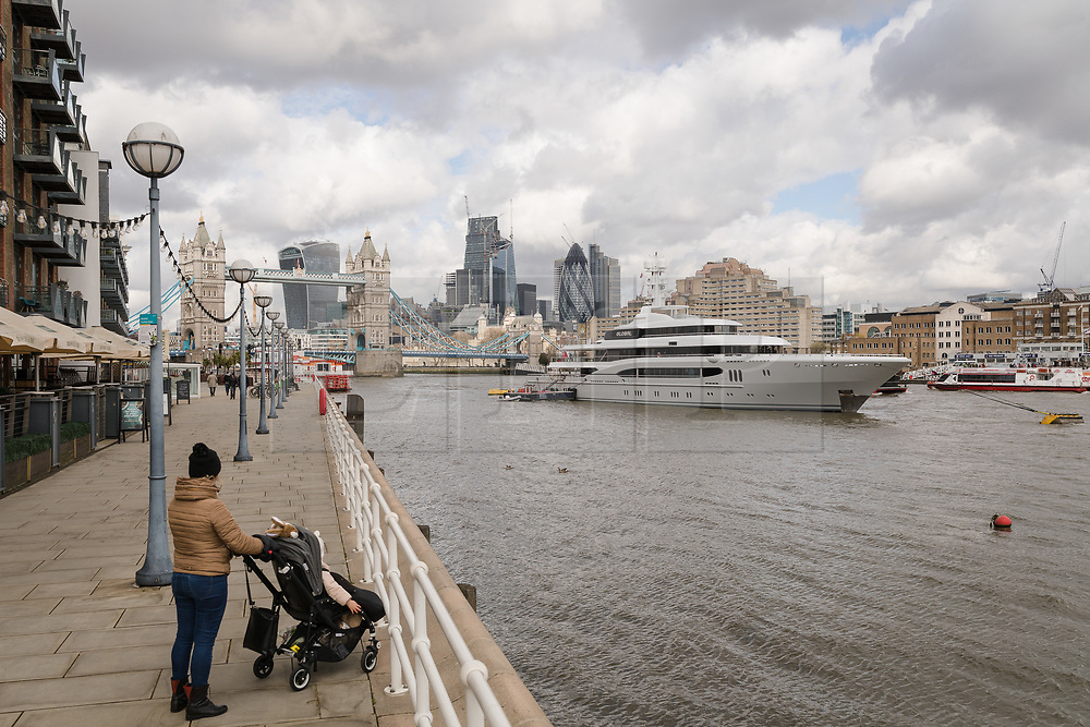 © Licensed to London News Pictures. 29/03/2018. London, UK. A woman and child look at the 220ft custom luxury superyacht, 'Global' moored at Butlers Wharf near Tower Bridge during a London visit. Previously named, Kismet during her last central London visit, she underwent a refit which saw her moved up 51 places in Boat International's list of top 200 largest super yachts in the world, boasting numerous luxuries such as a helipad, cinema and jacuzzi. Believed to be owned by Fulham Football Club chairman, Shahid Khan, Global can be chartered for an estimated £1m per week. Powered by 2 Caterpillar (3512 B) 2,038hp diesel engines and propelled by her twin screws propellers, Global is capable of a top speed of 15.5 knots, and comfortably cruises at 14 knots. . Photo credit: Vickie Flores/LNP