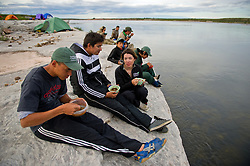 """Den First Nation youth eat dinner on the edge of  the Thelon river in August, 2011.  The Thelon is the largest and most remote game sanctuary in North America, which almost no one has heard of.  For the Akaitcho Dene, the Upper Thelon River is """"the place where God began.""""  Sparsely populated, today few make it into the Thelon. Distances are simply too far, modern vehicles too expensive and unreliable. For the Dene youth, faced with the pressures of a western world, the ties that bind the people and their way of life to the land are even more tenuous. Every impending mine, road, and dam construction threatens to sever these connections.(Photo by Ami Vitale)"""