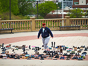 18 MAY 2020 - DES MOINES, IOWA: HEATHER RYAN sets up a memorial of empty shoes in front of the Iowa state capitol in Des Moines. Each Pair Iowa put together a memorial of empty shoes to represent Iowans killed by the COVID-19 pandemic. The memorial is traveling around the state. As of May 18, 355 people in Iowa have died from COVID-19, the disease caused by the Coronavirus (SARS-CoV-2), and 14,955 have tested positive for the Coronavirus.        PHOTO BY JACK KURTZ
