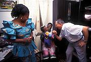 Caritas volunter (R) visiting a couple of Ghananian immigrants, jokes with their son in Nonantola, 1996...1996 Nonantola (Modena), un volontario della Caritas in visita presso una famiglia di immigrati ghanesi.