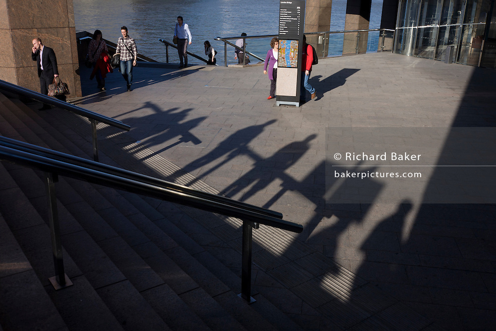 Man in red inspects a city map amid shadows and modernist architecture at number 1 London Bridge.