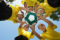 Five children (7-9 years) holding soccer ball, view from below, portrait