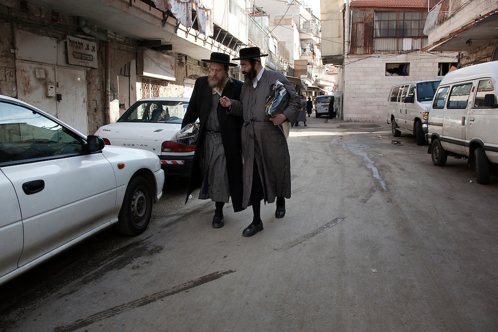 Two men waling down the street in Mea Shearim. Mea Shearim remains an Old World enclave in the heart of Jerusalem. The overwhelmignly Haredi population has preserved the traditional ways of life that existed for centuries among the Orthodox Jews of Eastern Europe. Life revolves around disciplined adherence to Jewish law, prayer and the study of Jewish texts. The residents follow strict dress and speech customs deriving from 17th century ghettos. Mea Shearim was established in 1874 as the second settlement outside the walls of the Old City.